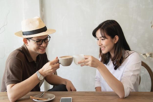 カジュアルな男と女のコーヒーを飲みながら楽しく話して