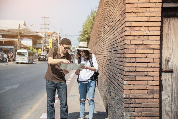 アジアカップル観光、道路を横断する市内地図を保持
