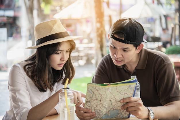 アジアのカップルはコーヒーショップで座って旅行を楽しむ