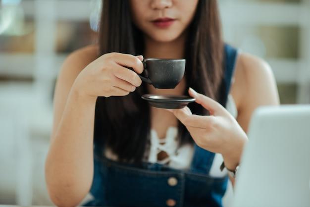 カフェでコーヒーカップを持つ女性を閉じる