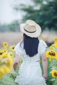ひまわり畑の上を歩いて白いドレスで美しいセクシーな女性