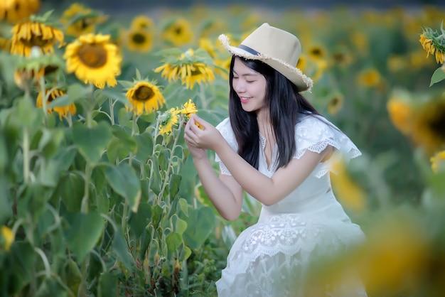 ヒマワリ、健康的なライフスタイルのフィールド上の白いドレスで美しいセクシーな女性
