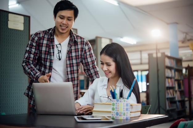学んでいる若い学生、図書館の本棚