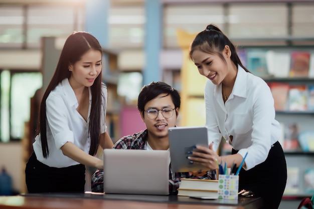 Молодые студенты учатся, книжные полки библиотеки