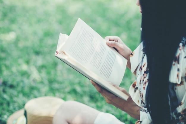 Красивая девушка читает книгу в парке в летнем солнечном свете