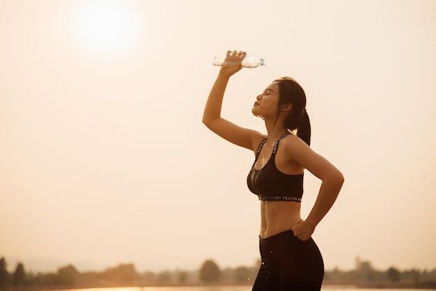 若い女の子がジョギング中に水を飲む