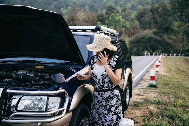 アジアの女性が地元の道路上の車のエンジンの問題を解決するために修理担当者または保険スタッフを呼び出す