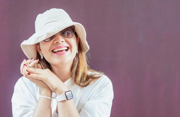 白い帽子とサングラスと白いドレスを持つ女性