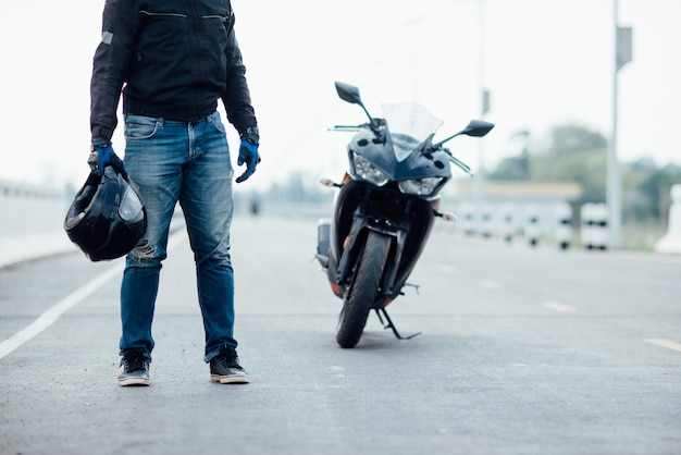 オートバイの手の中にヘルメットとハンサムなバイク