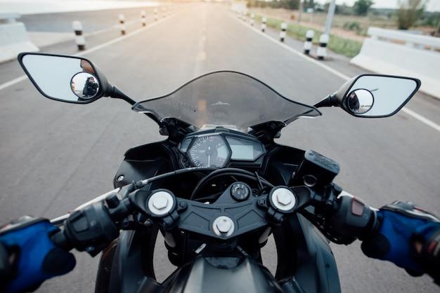 Наездник на мотоцикле по дороге катается. весело проводя время на пустой дороге