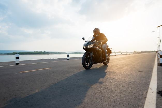 ロードライディングでライダーバイク。空の道を運転して楽しんで