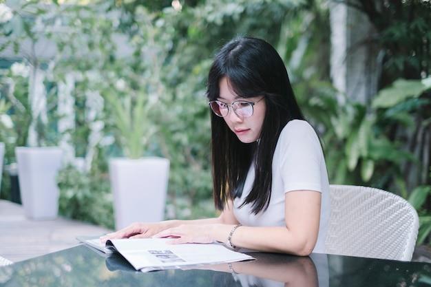 Девушка в очках читает книгу в саду