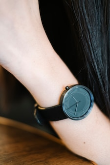 女の子の手に最小限の古典的な黒時計