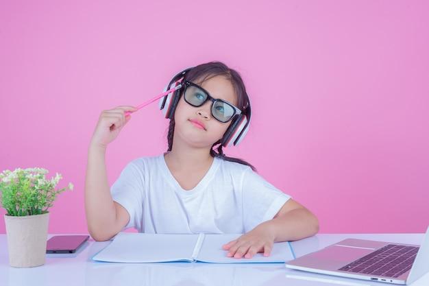 女の子はピンク色の背景に本を書きます。