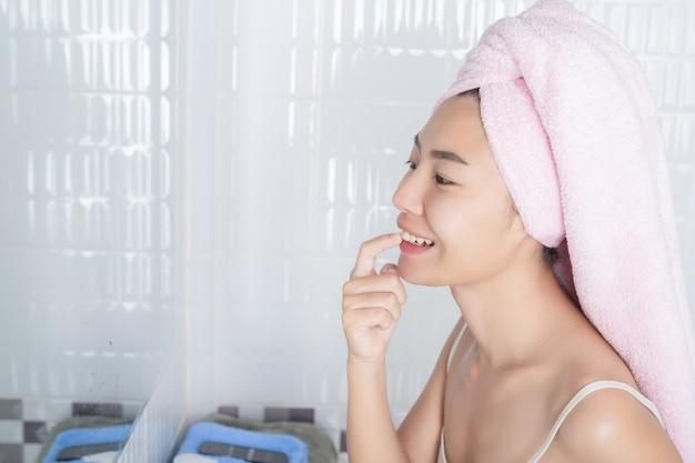 Азиатская девушка моет лицо.