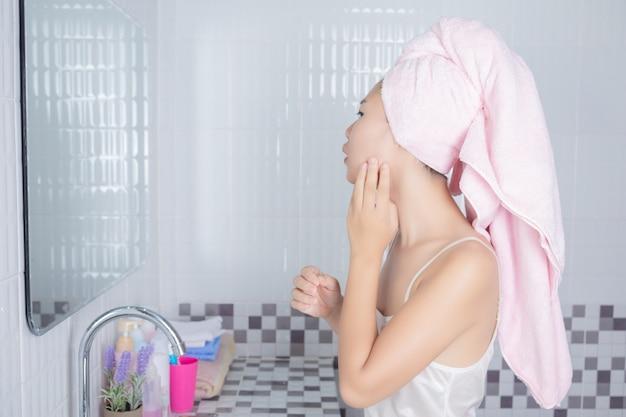 アジアの女の子はにきびを絞る。