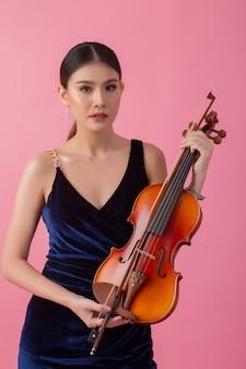 美しい若い女性がバイオリンを弾く