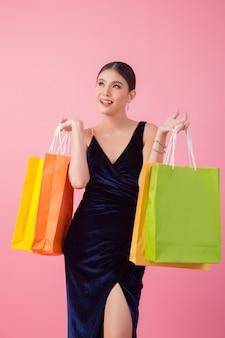 幸せな笑顔の女性の肖像画は買い物袋を保持します。