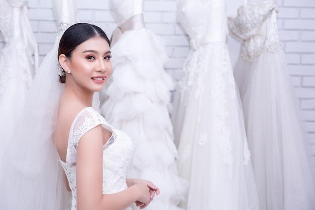 Азиатская молодая женщина примеряет свадебное платье на современной свадьбе