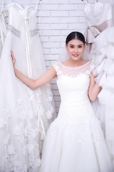 モダンな結婚式でウェディングドレスを試着しているアジアの若い女性の花嫁