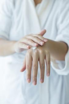女性は彼女の手に化粧品クリームの瓶を保持します。