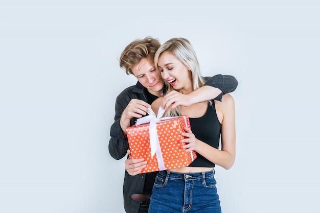 幸せな若いカップルの肖像画が一緒にギフトボックスとサプライズを愛する