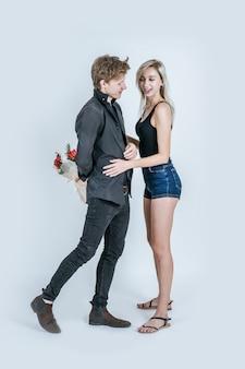 花と一緒に愛する幸せな若いカップルの肖像画