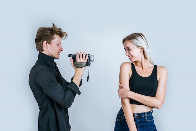 ビデオカメラとレコードクリップビデオを保持しているカップルの幸せな肖像画