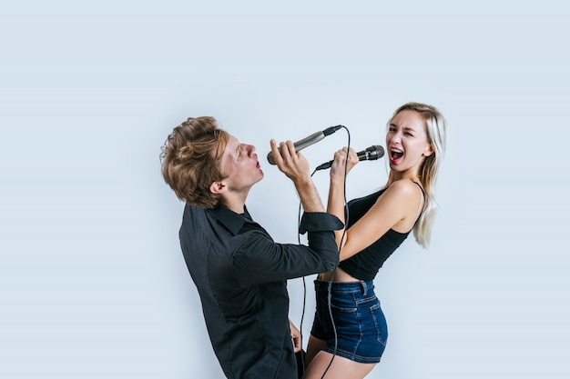Счастливый портрет пары, держащей микрофон и поют песню