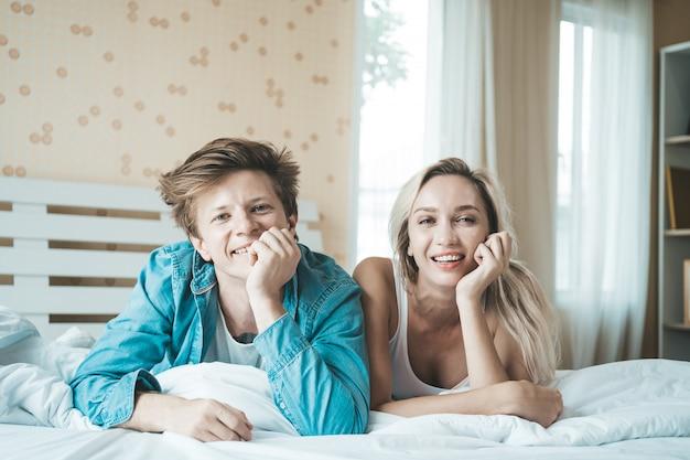 幸せなカップルが寝室で一緒に遊んで