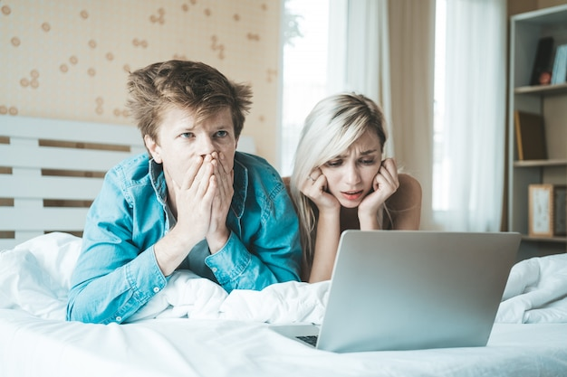 幸せなカップル、ベッドの上にラップトップコンピューターを使用して