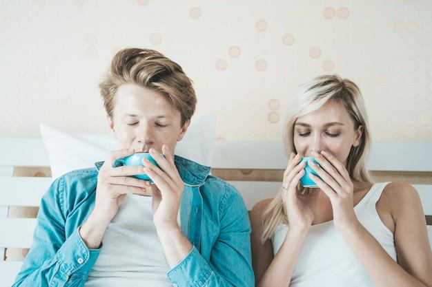 幸せなカップルの手持ち株カップと朝のコーヒーを飲む