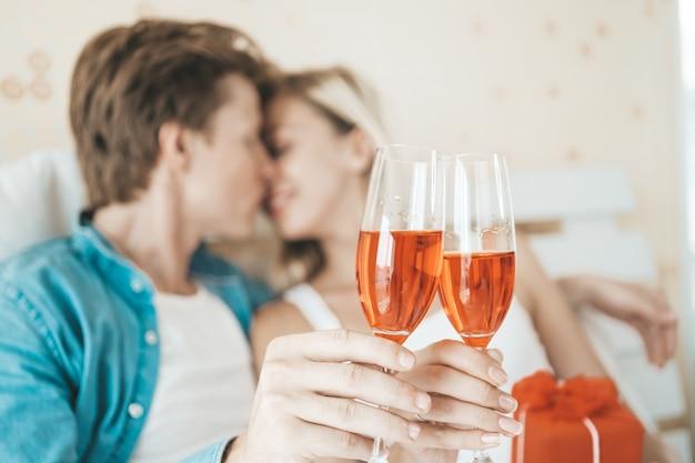 幸せなカップルの寝室でワインを飲む