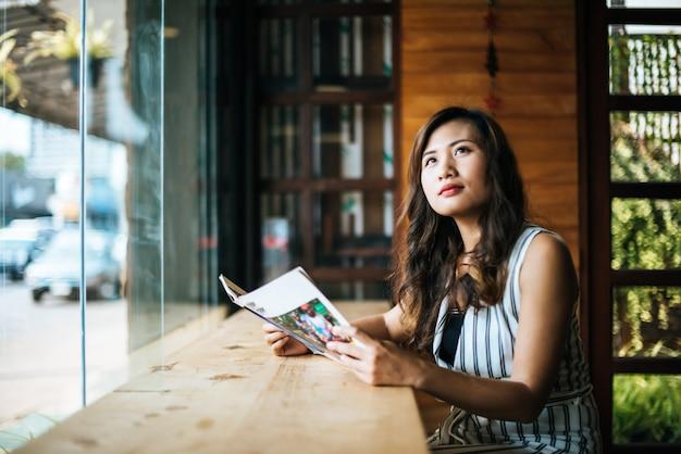 美しい女性のカフェで雑誌を読む