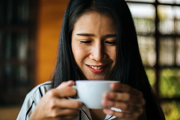 笑みを浮かべて肖像画アジア女性のコーヒーショップカフェでリラックス