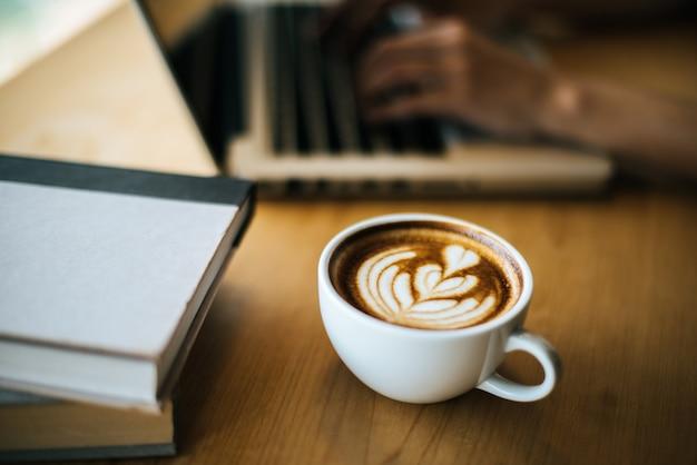 Латте арт в чашке кофе на столике в кафе