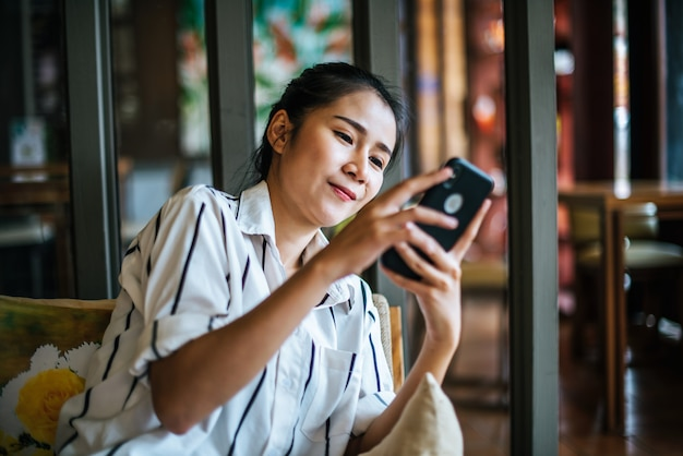 Женщина сидит и играет ее умный телефон в кафе