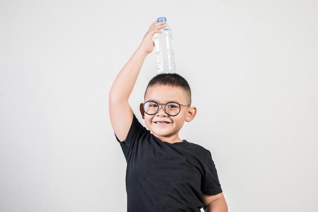 スタジオ撮影で水のボトルを持つ面白い少年