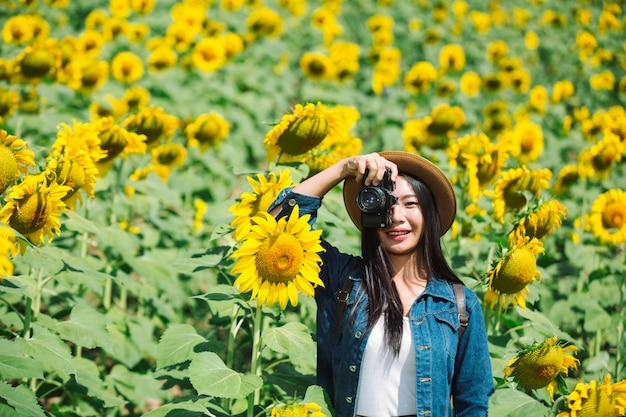 女の子はひまわり畑で写真を撮って幸せです。