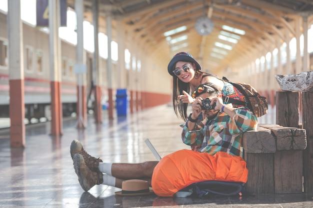 Путешественники фотографируют пары в ожидании поезда.