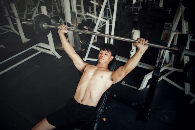 スポーツジムでハンサムなトレーニング機器