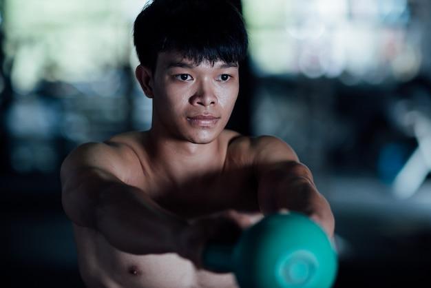 スポーツウェア、ジムでのエクササイズクラスの若い男