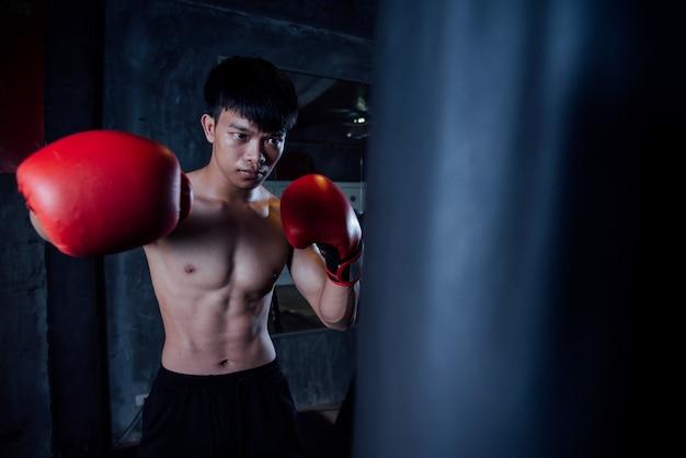 若い男の強いスポーツ男ボクサーはジム、健康的な概念の練習をする