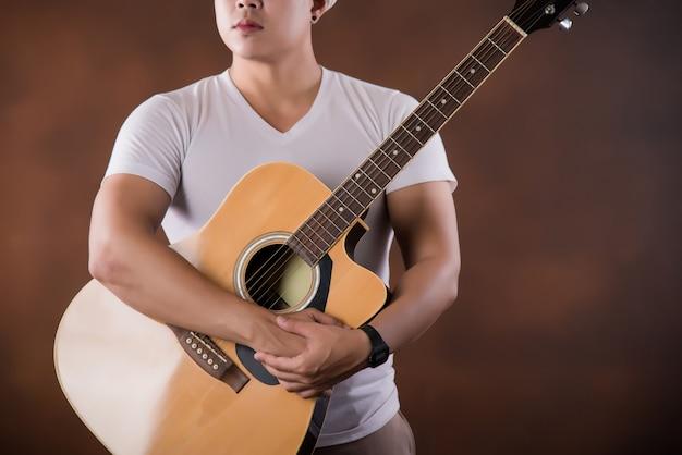 Азиатский молодой человек музыкант с акустической гитарой
