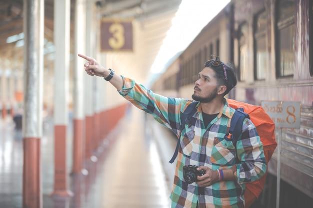 電車を待っている間旅行者はカップルの写真を撮る。