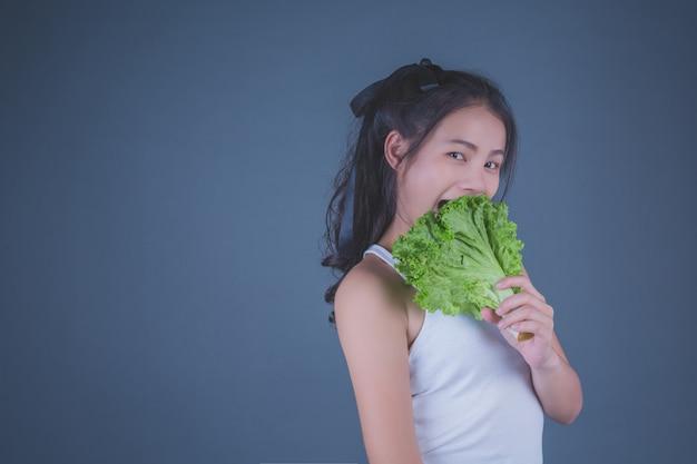 女の子は灰色の背景に野菜を保持します。