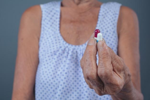 年配の女性が薬を服用しています。