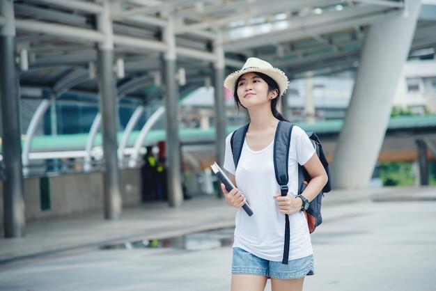 Счастливая усмехаясь азиатская девушка студента с рюкзаком на предпосылке города