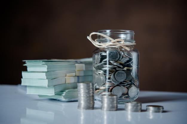 お金の節約の概念でコインと現金のボトル