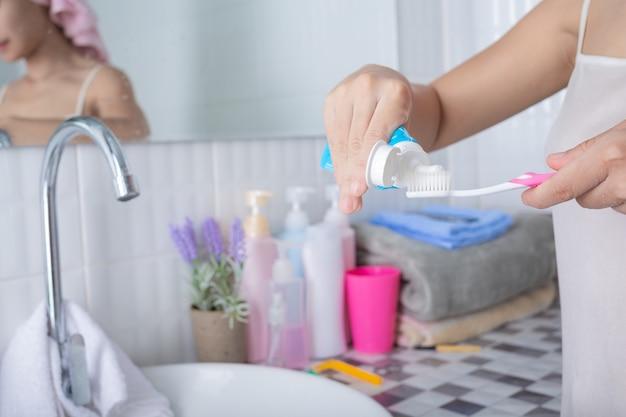 若い女性が歯を磨きます。